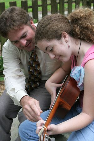teenaged girls: A father teaching his daughter to play guitar.