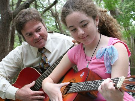 teenaged girls: A father and daughter playing guitar together under the trees. Stock Photo
