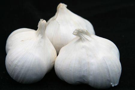 spicey: Tre bulbi d'aglio nei confronti di uno sfondo nero.