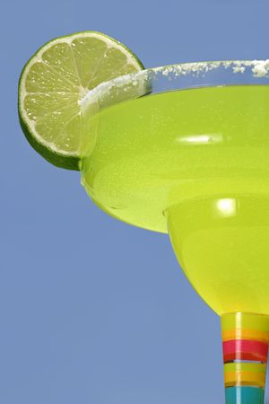 A bright green margarita with a lime against a vivid blue sky. photo