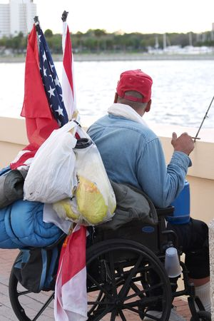 Homeless veteran in a wheelchair looking out at the ocean.