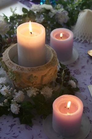 cater:  nice arrangement of lavendar candles with flowers and a wedding bell on a table. Stock Photo