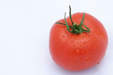 dewdrops: A ripe red tomato with dewdrops on it, against a white background.