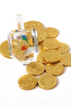 A fancy, crystal dreidel for Hanukkah, along with chocolate coins (gelt). (trademarks removed, only hebrew symbols left) Stock Photo - 205795