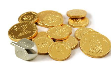 jewish: A dreidel and gold chocolate Hanukkah gelt. (trademarks removed, only hebrew symbols left) Stock Photo