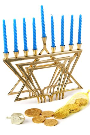 A Hanukkah menorah, dreidel, and bag of gelt (chocolate coins).  Isolated. (trademarks removed, only hebrew symbols left) Stock Photo