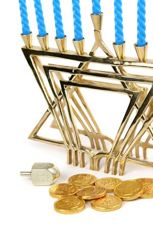 A menorah with candles along with a dreidel and chocolate Hanukah gelt. Isolated. (trademarks removed, only hebrew symbols left) photo