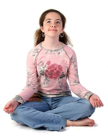 A teenaged girl with her legs crossed and palms extended in meditation.  Isolated