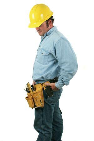 下へ見ている用具ベルトと建設労働者。 分離されました。 写真素材