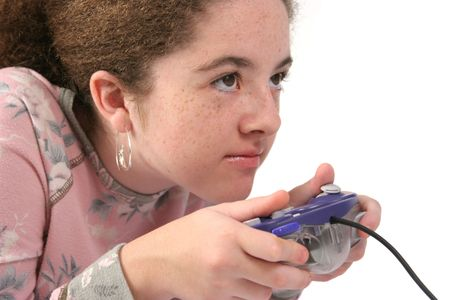 teenaged: A teenaged girl holding a game controller, with an intense look of concentration.  Isolated.