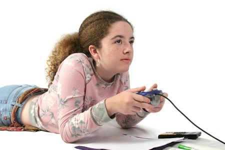 teenaged girls: A student playing video games instead of doing her math homework. Stock Photo