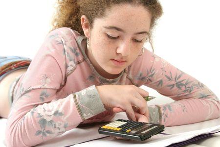 teenaged: A teenaged girl studying math, using a calculator.