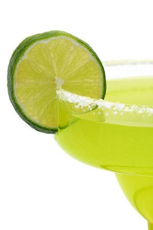 A closeup of a lime on the salty rim of a margarita glass - Isolated against a white background.