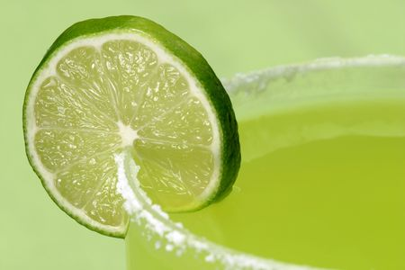 quench: A closeup of a juicy lime on the salty rim of a margarita glass.