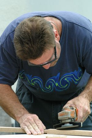 sander: A photo of a man, wearing safety goggles, and using a sander on some wood.