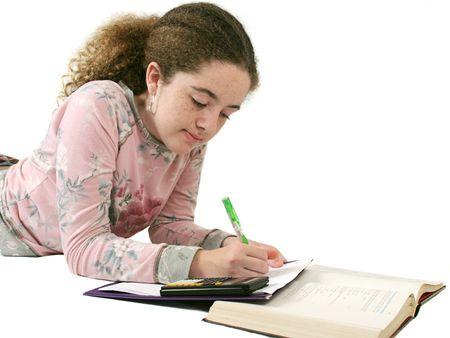 A teenaged girl doing her homework.  Isolated. Stock Photo
