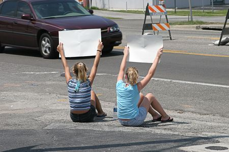teenaged girls: Two teenaged girls holding signs for passing traffic.