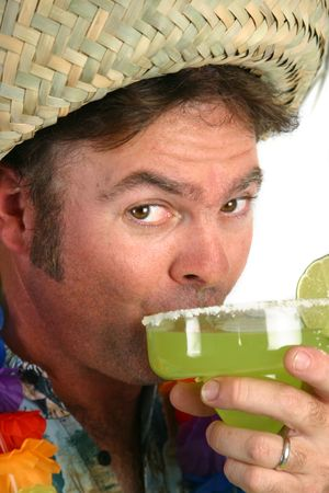 andamp: A man in a straw hat, hawaiian shirt andamp,amp, lei, taking a sip from a margarita.
