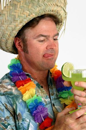 tipsy: A man in a Hawaiian shirt with a straw hat and lei, drooling over a margarita hes about to drink. Stock Photo