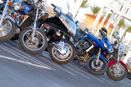 Five shiny, colorful motorcycles parked side by side.