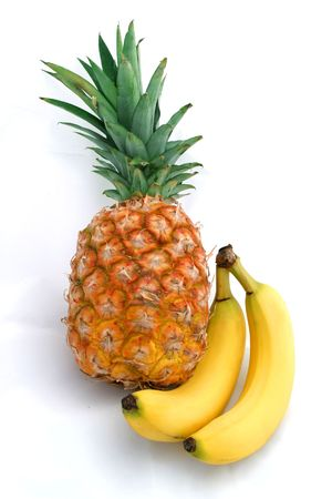 A whole pineapple posed with two perfect yellow bananas against a white background. photo