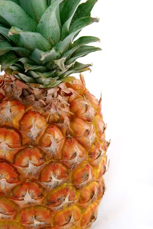 A two thirds closeup view of a pineapple against a white background. photo