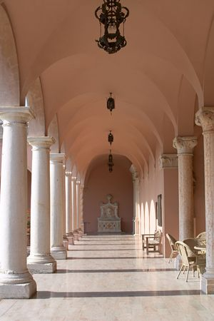 palatial: View down a hallway in a pink marble, venetian style palazzo.