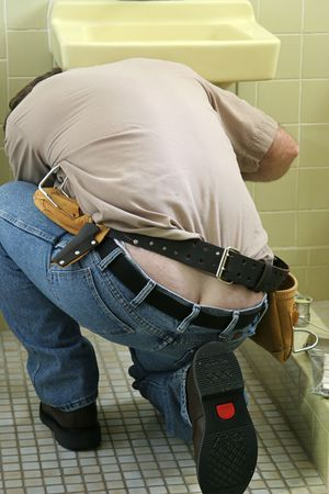 crack: A plumber bending over to fix a sink. His butt crack is showing.