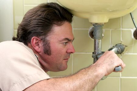 A closeup of a plumber using a wrench to tighten a pipe. photo