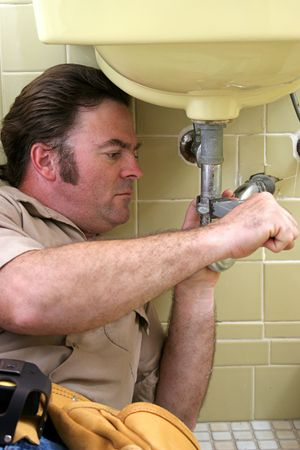 A plumber using a pipe wrench to repair a sink. photo