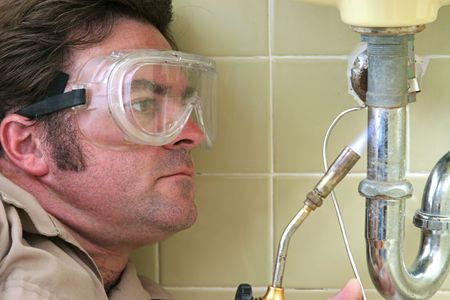 torches: A plumber using a welding torch to solder a pipe. Stock Photo