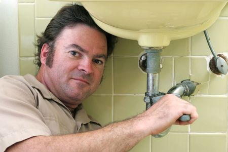 A plumber working on a pipe under a bathroom sink. photo