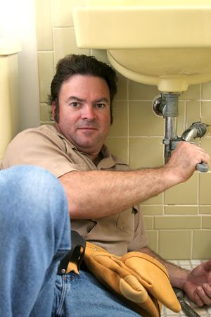 A plumber using a wrench to tighten a pipe under a sink. photo