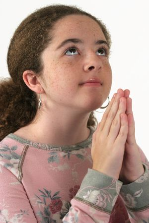 looking upwards: A teenaged girl, hands folded in prayer, looking upwards. Isolated.