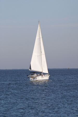 a sailboat in full sail, heading into the horizon. photo