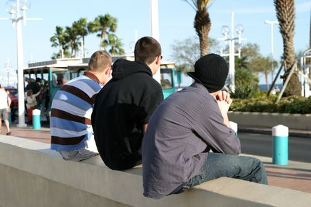 loitering: three guys sitting on a wall, watching people pass by on the street. Stock Photo