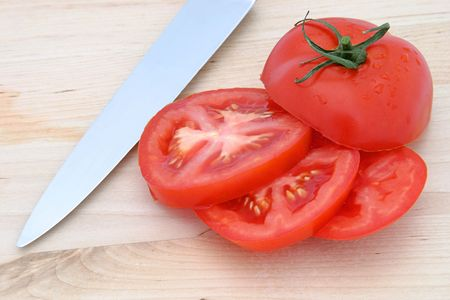 A sliced ripe tomato on a cutting board with a knife. photo