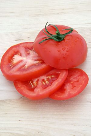 A sliced tomato arranged on a wooden cutting board.