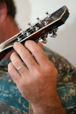 mandolin: a closeup of a mans hand tuning a mandolin. Stock Photo