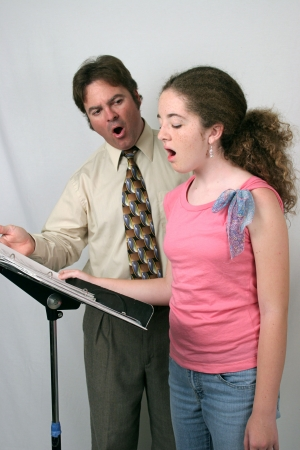 choral: A voice teacher instructing a student. They are making the Ahhh sound.
