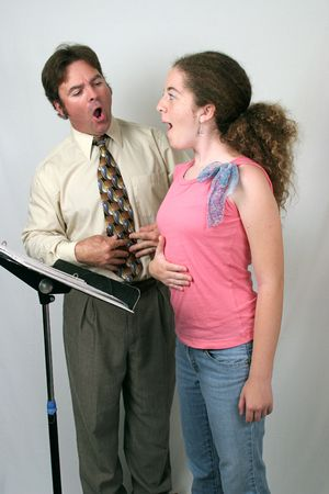 A voice teacher showing a student how to breath from her diaphragm.