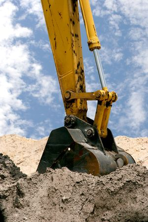 hoe: A back hoe digging in piles of dirt. Stock Photo