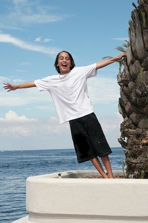 youthful: A boy leaning from a palm tree with his arms extended, symbolizing freedom and youthful exuberance.