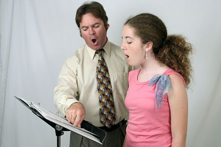 A voice teacher demonstrating to a student how to make the Ohhh sound.