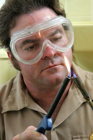 butane: A welder, wearing safety goggles, lighting a welding torch.