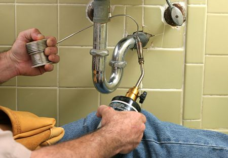 solder: A plumber using a welding torch to solder pipe. Stock Photo
