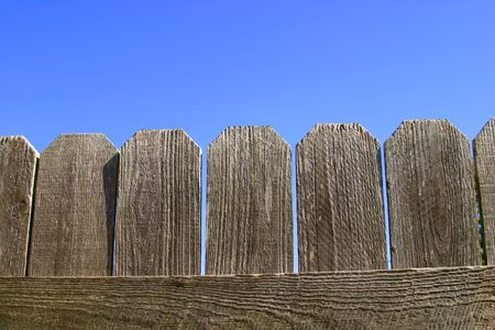 lumber room: a closeup of a wooden fence against a vivid blue sky. a background with room for text.