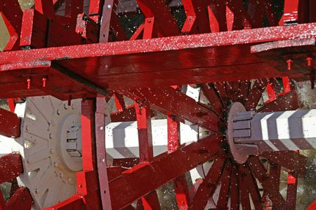 churning: a closeup of a paddle wheel, captured in motion with water churning and spraying through it.