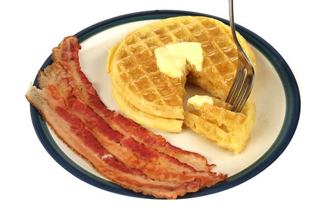A plate of waffles and bacon, with a bite of waffle about to be eaten.