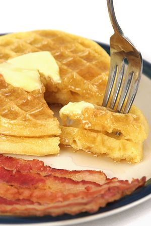 A vertical, closeup view of a bite of waffles dripping with syrup on a plate with bacon. Imagens